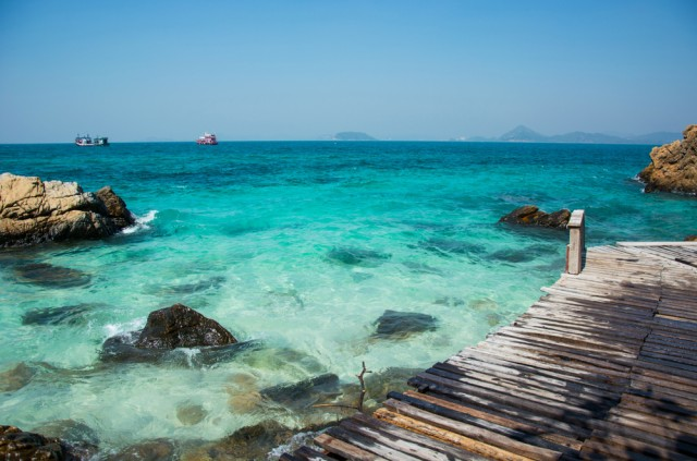Rocks,And,Wooden,Bridge,On,The,Beach,With,Clear,Sea